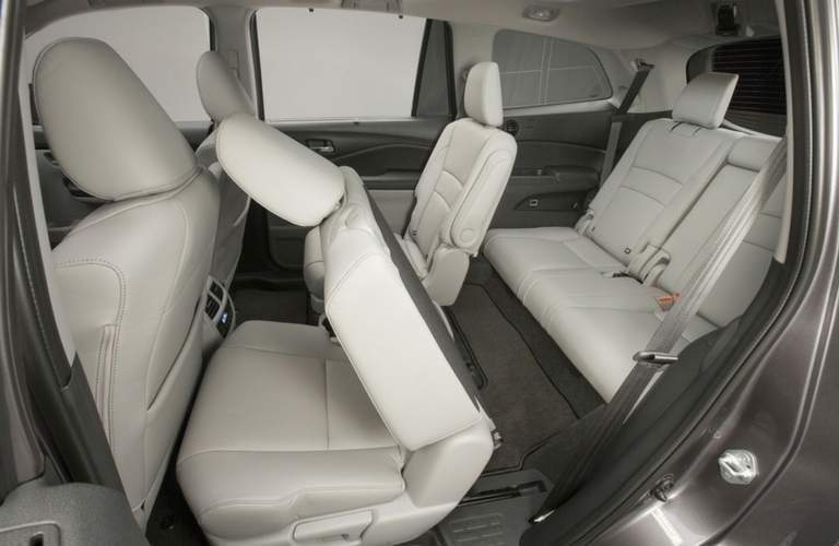 view of the seating area inside the 2018 Honda Pilot with a second row seat folded forward allowing a view of the third row seat