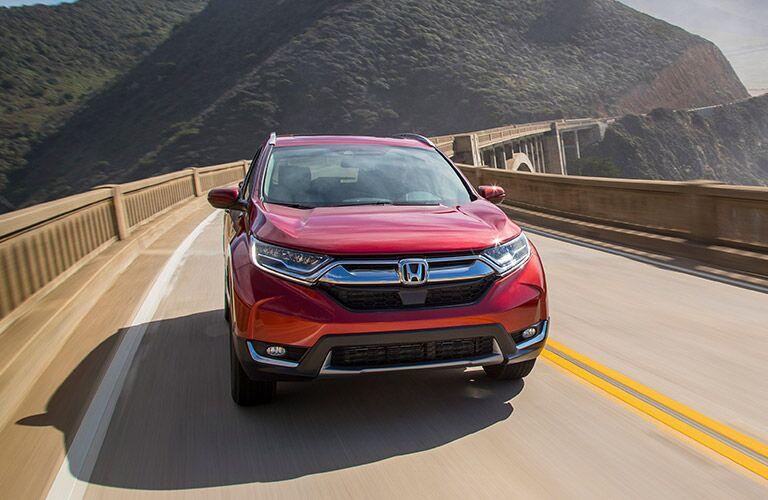 Red 2019 Honda CR-V drives up a curvy highway through mountains.