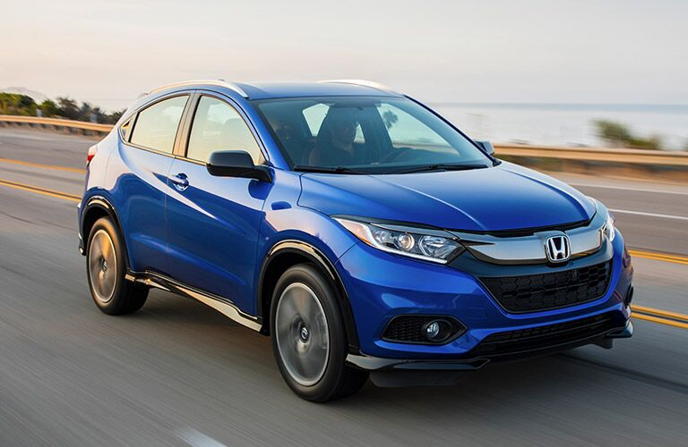 Exterior shot of a blue 2019 Honda HR-V driving down a highway.