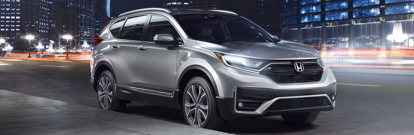 Silver 2020 Honda CR-V parked by a sidewalk in a city at night.