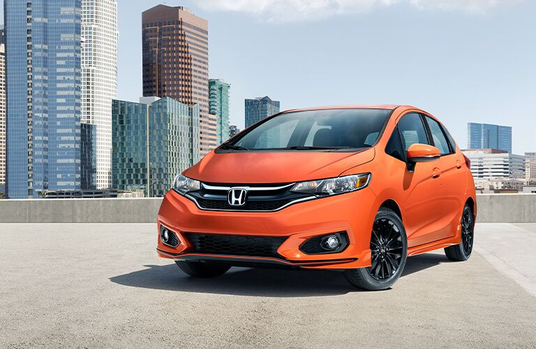 Orange 2020 Honda Fit parked on a city rooftop.