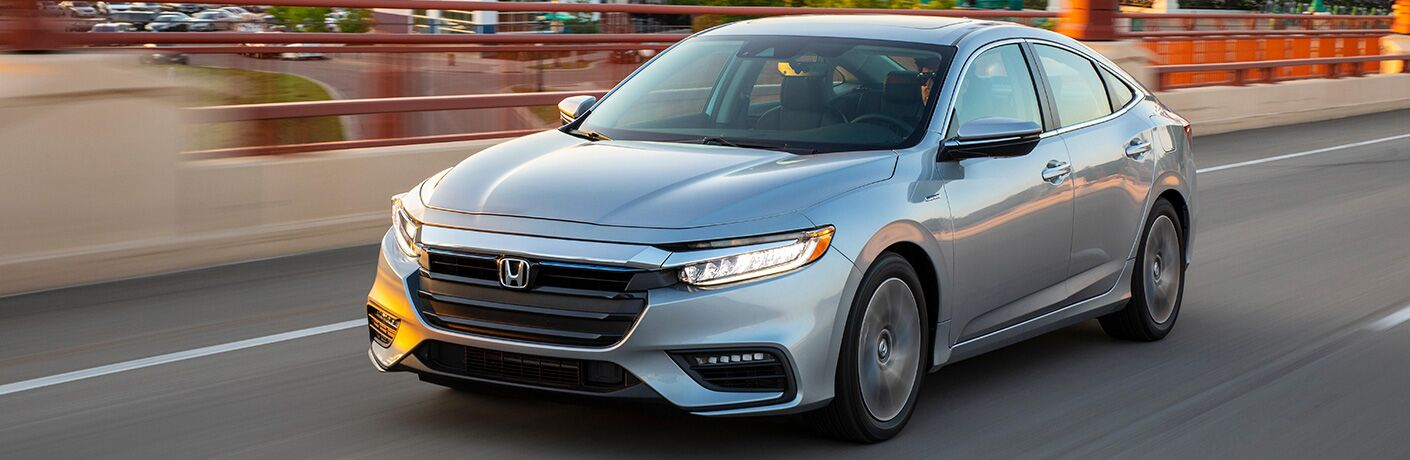 Silver 2020 Honda Insight drives up a sunny highway.