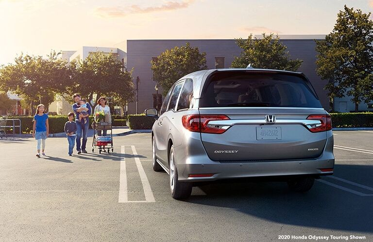 A family exits a store and walks to their 2020 Honda Odyssey in the parking lot as the sun sets.