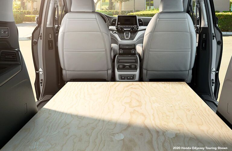 A large wooden board fills the cargo area of a 2020 Honda Odyssey.