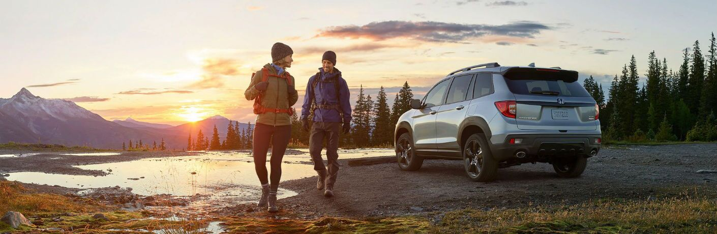 Two people walk away from a silver 2020 Honda Passport parked in nature.