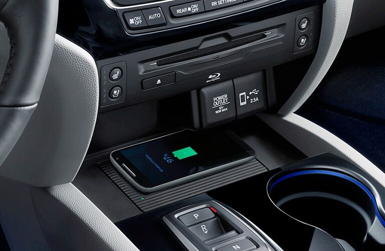 A smart device charges wirelessly on the center console of the 2020 Honda Pilot.