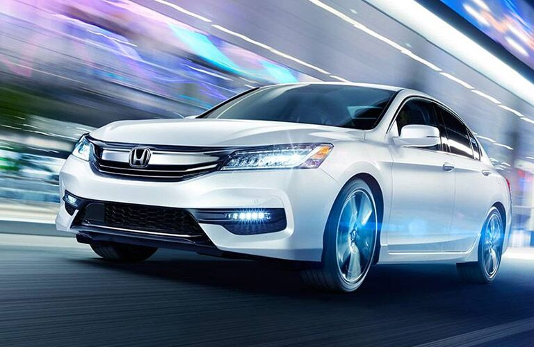 White Honda Accord cruises at high speed up a multicolored tunnel.