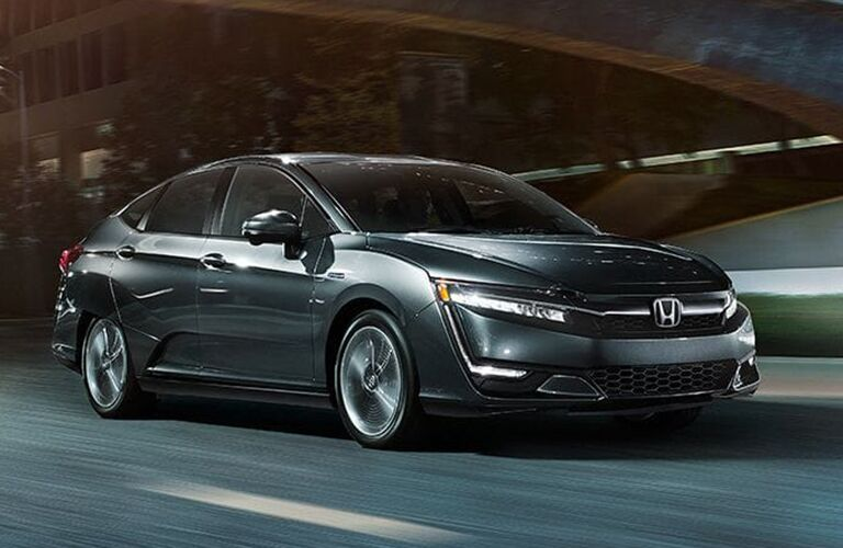 Greenish Honda Clarity drives down a highway at night.
