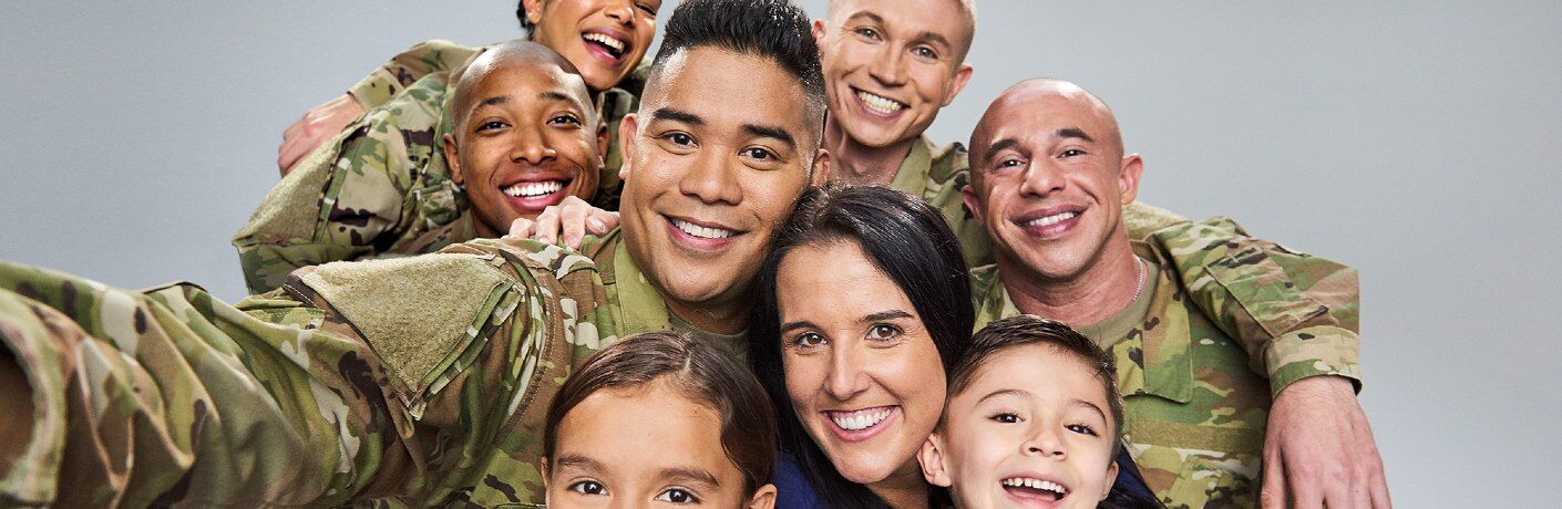 A soldier takes a selfie encompassing his diverse, happy military buddies along with his family.
