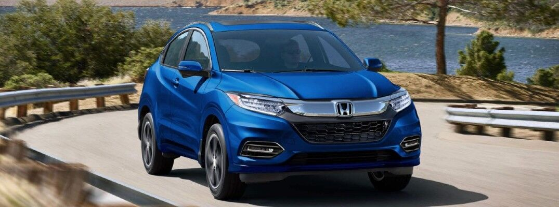 Blue 2020 Honda HR-V drives up a winding highway.
