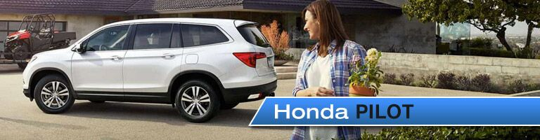"Woman holding a plant looking at the Honda Pilot parked behind her. Image labeled ""Honda Pilot"""