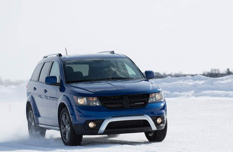 Blue Dodge Journey driving on snowy road