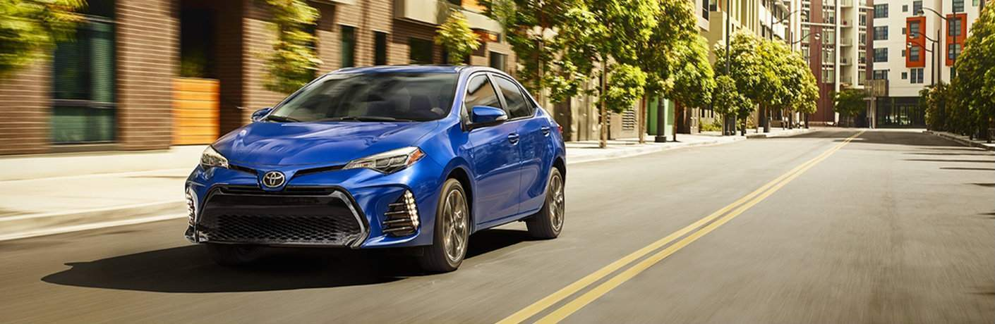 A front left quarter image of a blue 2018 Toyota Corolla driving through a city