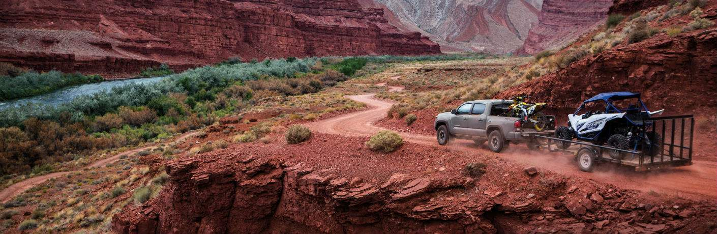 A photo of the 2018 Toyota Tacoma pulling a trailer through the desert along a trail