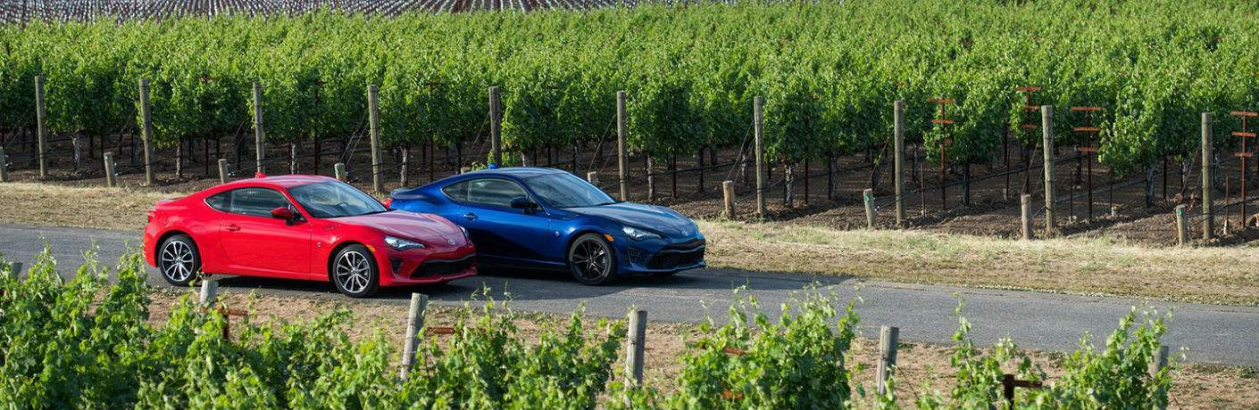 A photo of a red and blue 2018 Toyota 86 parked between two vineyard fields