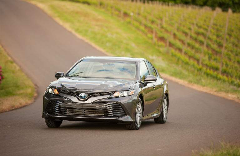 A head-on view of the 2018 Toyota Camry Hybrid driving past a vineyard