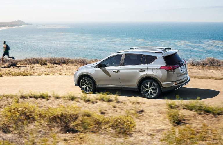 A left profile view of a 2018 Toyota RAV4 driving on a dirt road near the ocean