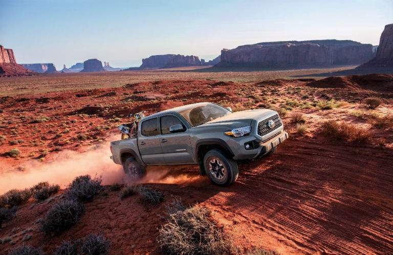 A right profile view of a very dusty 2018 Toyota Tacoma hauling a dirt bike through the desert