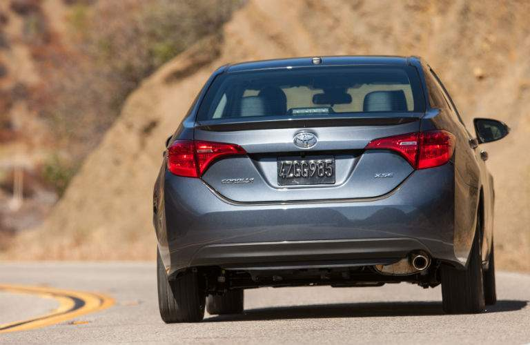 A rear view of the 2018 Toyota Corolla driving on a curvy road in the hills