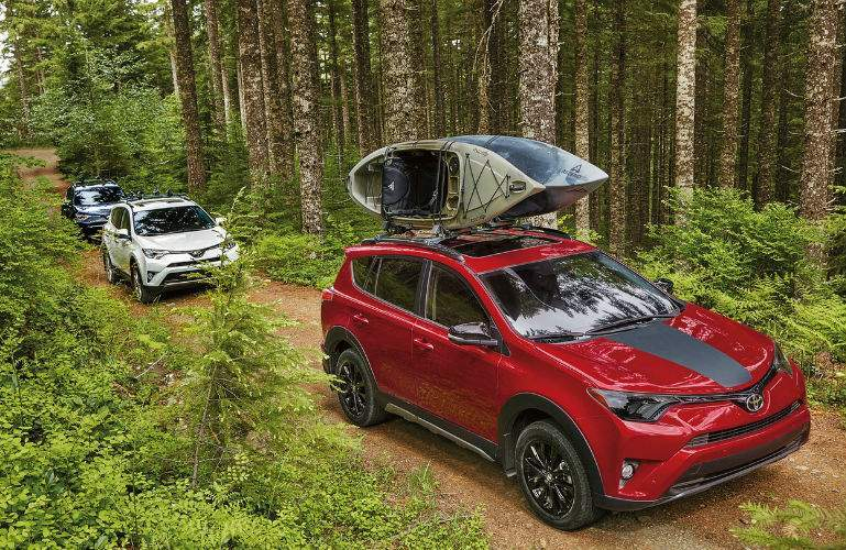 A photo of three different versions of the 2018 RAV4 driving through the woods