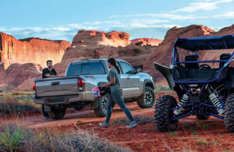 A photo of people unloading their off-road gear from a 2018 Toyota Tacoma in the desert