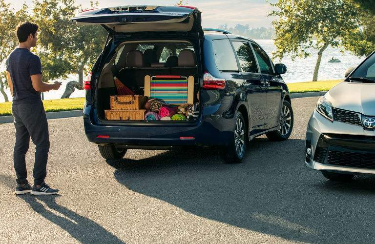 A man looking inside of the 2018 Toyota Sienna that is filled with picnic supplies