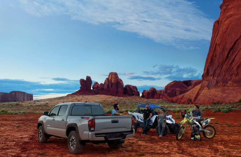 People relaxing around a 2018 Toyota Tacoma after riding their off-road vehicles through the desert
