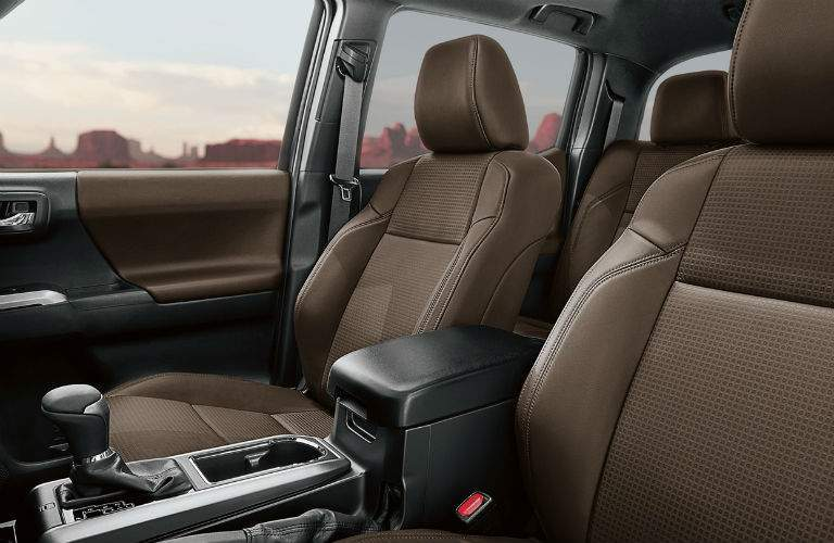 A view from the driver's side of the 2018 Toyota Tacoma showing a special interior material and the center console.