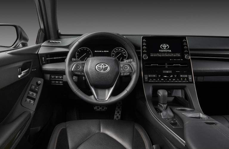 An interior photo of the driver's cockpit in the 2019 Avalon showing the vehicles center gauge cluster and large touchscreen