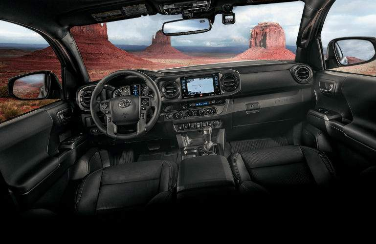 A photo of the dashboard, steering wheel and center gauge cluster of the 2018 Tacoma