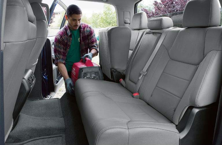 A young man places a piece of equipment in the back seat of the 2018 Tundra taking advantage of its flip-up seats