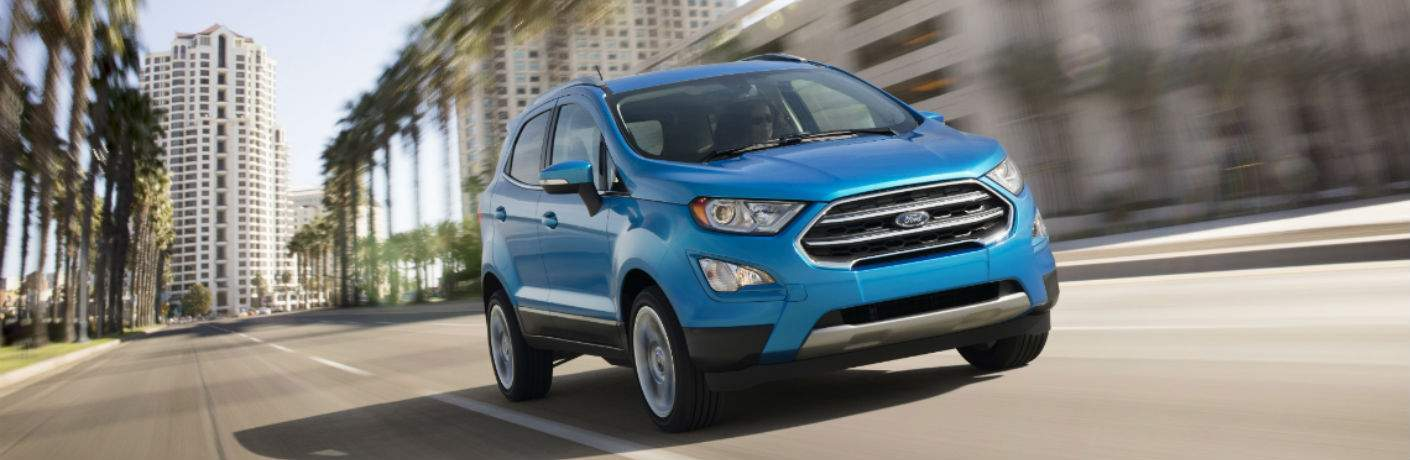 A blue 2018 Ford EcoSport driving down an urban street coming at the camera