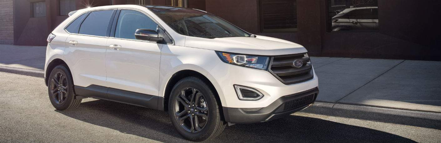 A right profile photo of a white 2018 Ford Edge parked on a city street