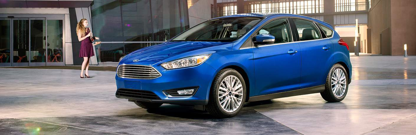 A left quartering profile view of a blue 2018 Ford Focus hatchback in front of a building
