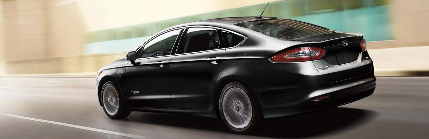 A left profile photo of a black 2018 Ford Fusion Energi in motion driving down the road