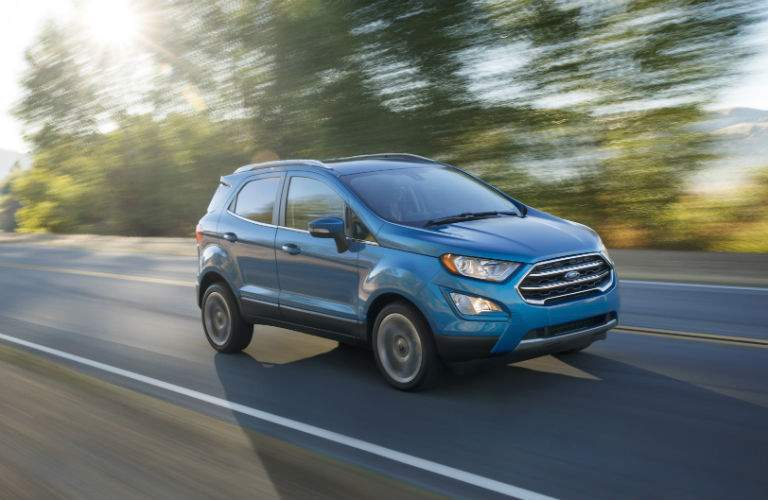 A right profile view of a light blue 2018 Ford EcoSport driving on a country road.