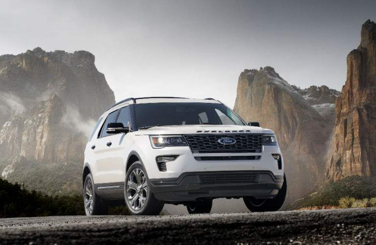 A front right quarter view of a white 2018 Ford Explorer in front of some mountains