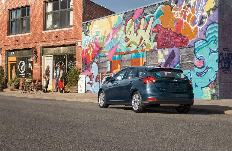 A rear quarter view of the dark blue 2018 Ford Focus hatchback in front of a mural