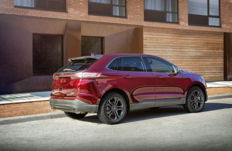 A right profile view of a red 2018 Ford Edge parked in front of an apartment building