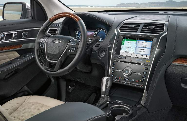 An interior view of a 2018 Ford Explorer showing the infotainment system, steering wheel and center gauge cluster