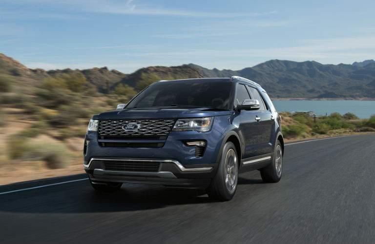 A dark blue 2018 Ford Explorer driving on a road in the desert near a lake and mountains