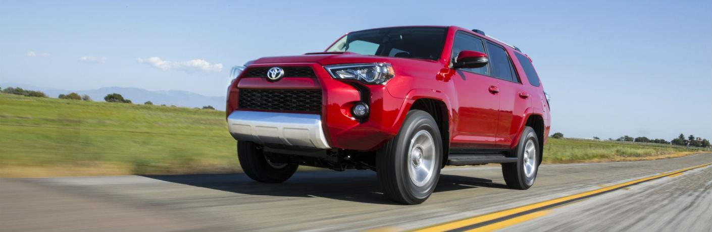 A front left quarter view of a red 2018 Toyota 4Runner driving on a road