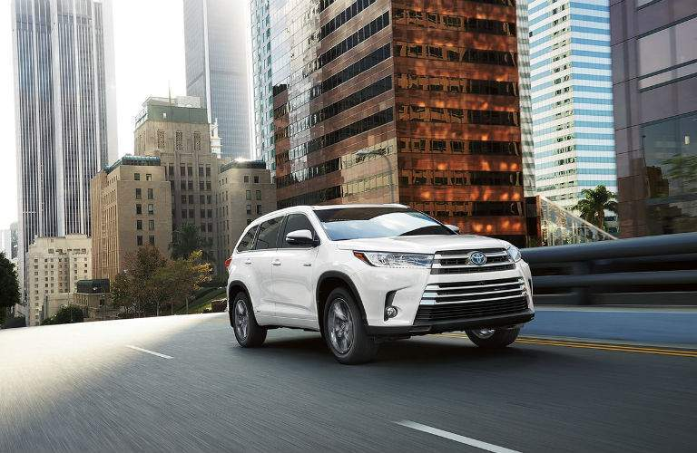 A front quarter image of a white 2018 Toyota Highlander driving through an urban setting