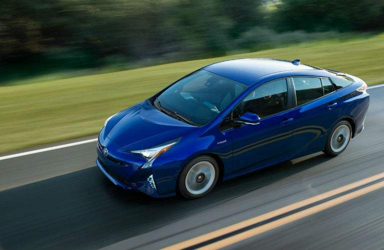An overhead view of a blue 2018 Toyota Prius driving on a country road