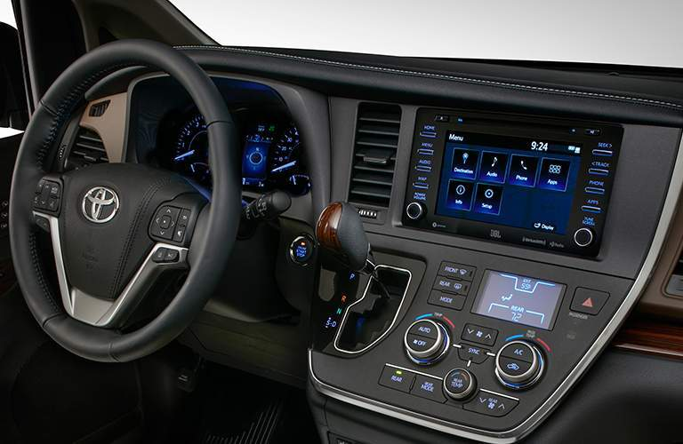 A view of the dashboard, steering wheel and infotainment system found in the 2018 Sienna