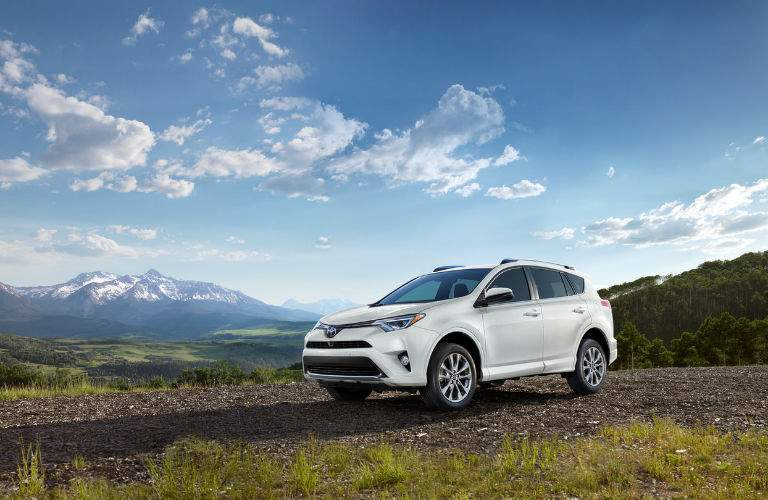 A white 2018 Toyota RAV4 on a desolate road with mountains in the background