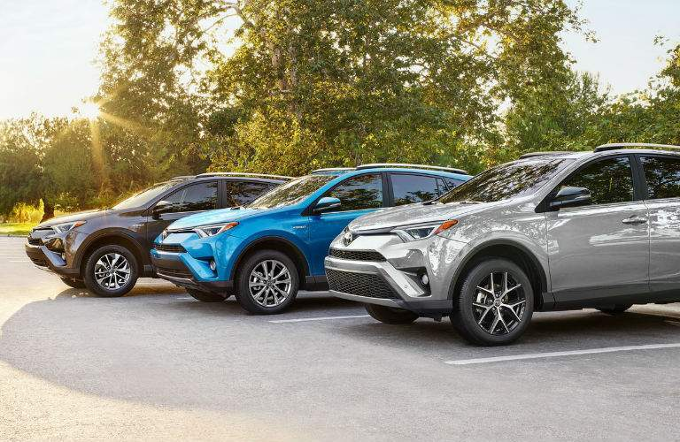 Three versions of the 2018 Toyota RAV4 side by side in a parking lot