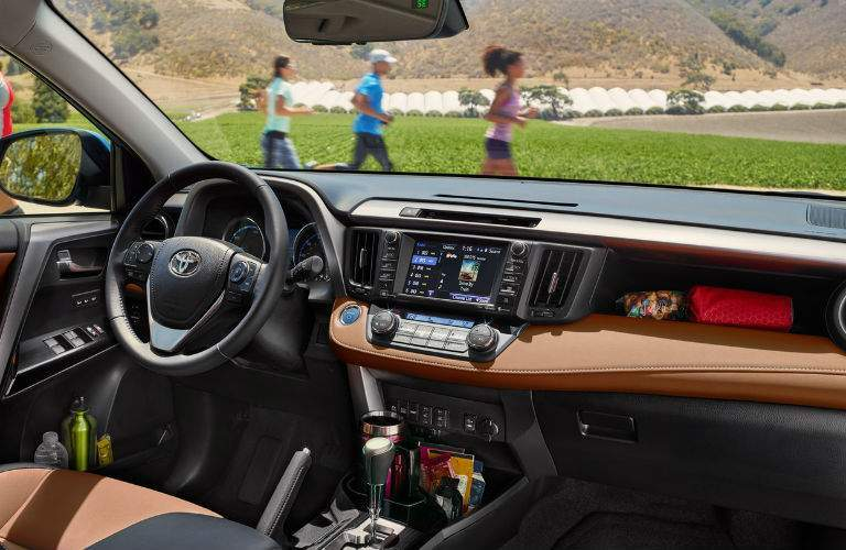 A view of the dashboard of the 2018 Toyota RAV4 showing the infotainment system's touchscreen and various storage compartments