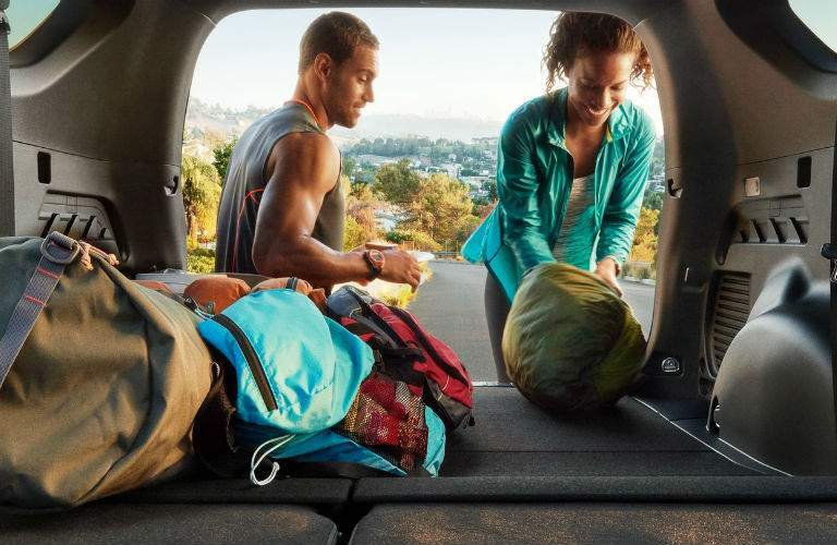 A photo of the rear cargo area in the 2018 Toyota RAV4 with the rear seats folded down and dufflebags inside of it