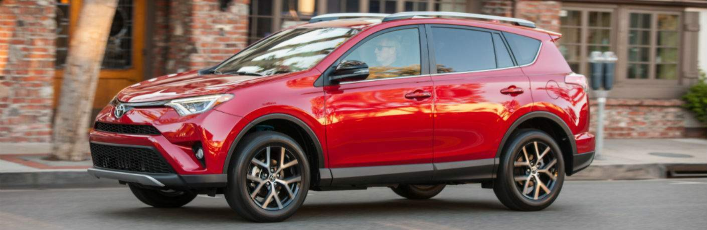 A left profile view of the 2018 Toyota RAV4 on a city street in front of a red brick building